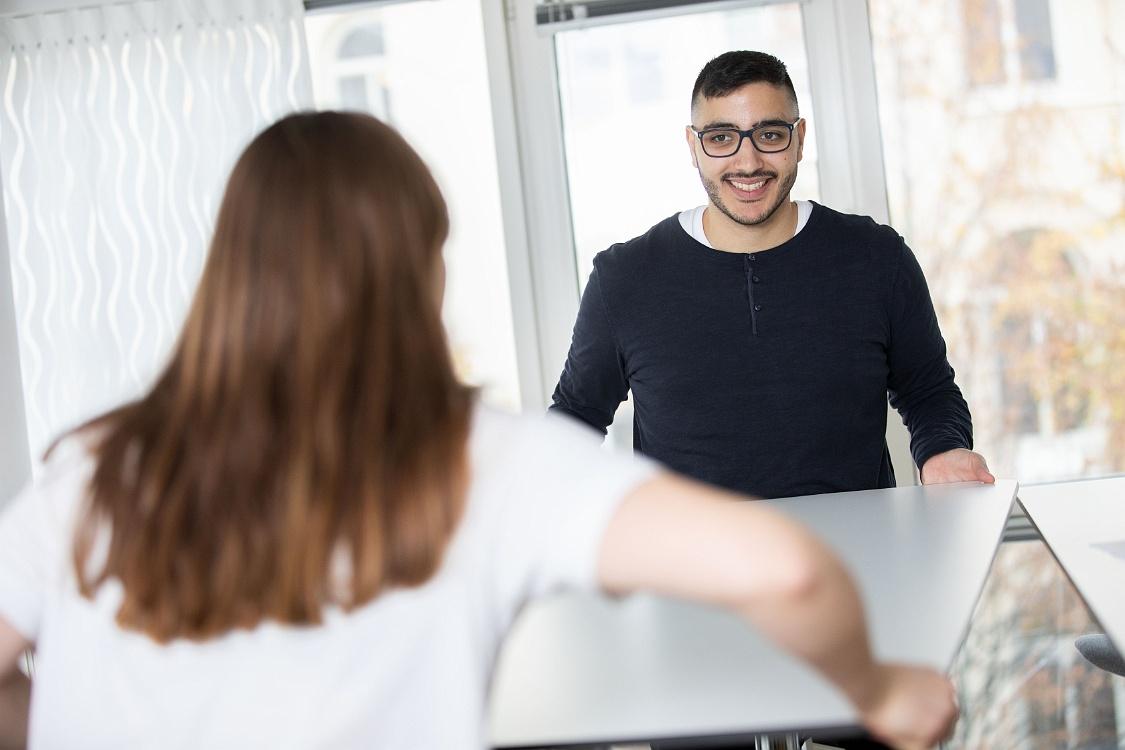 En kvinna med ryggen mot kameran hjälper en man som ser glad ut att lyfta och flytta ett bord