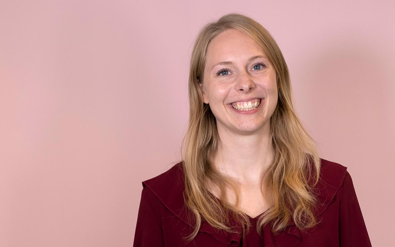 En glad kvinna står. mot rosa bakgrund och ler in i kameran.