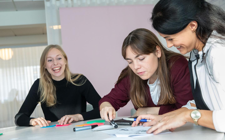 Tre engagerade och glada kvinnor sitter bredvid varandra vid mötesbord och en förklarar något på ett papper