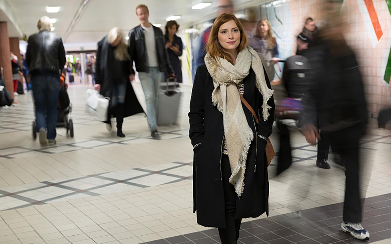 Kvinna klädd i kappa som går i gången mellan centralstation och tunnelbana med många människor runt omkring