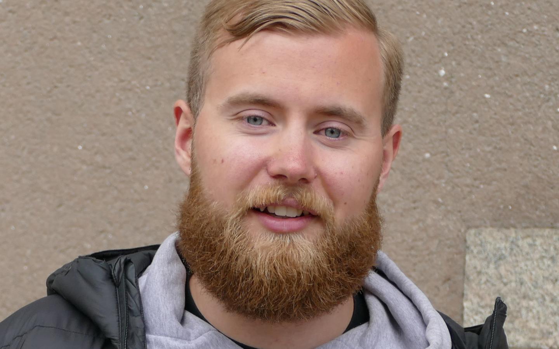 Närbild utomhus på en mans ansikte som har rötthår och skägg