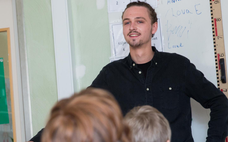 Man som är vikarie och som står framför en whiteboard och tittar ut mot eleverna i ett klassrum
