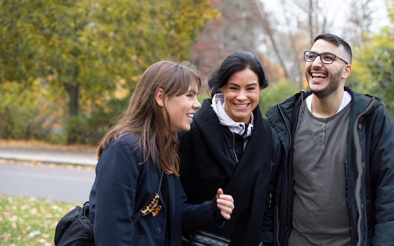 Två kvinnor och en man står nära varandra utomhus en höstdag och skrattar tillsammans