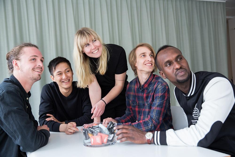 Fem personer som är vikarier står och sitter runt ett bord och har möte