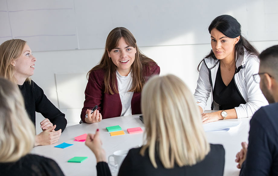 fyra kvinnor som sitter runt ett mötesbord och diskuterar engagerat