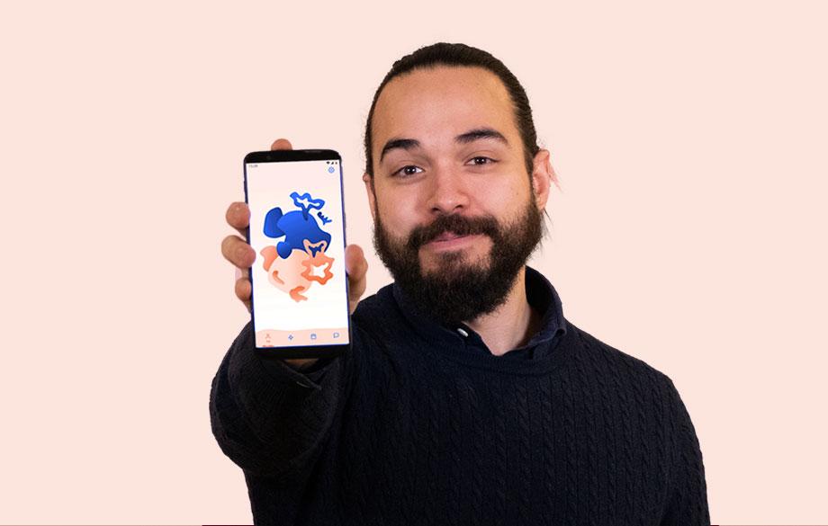 man som håller fram mobilen och visar pamoja-appen