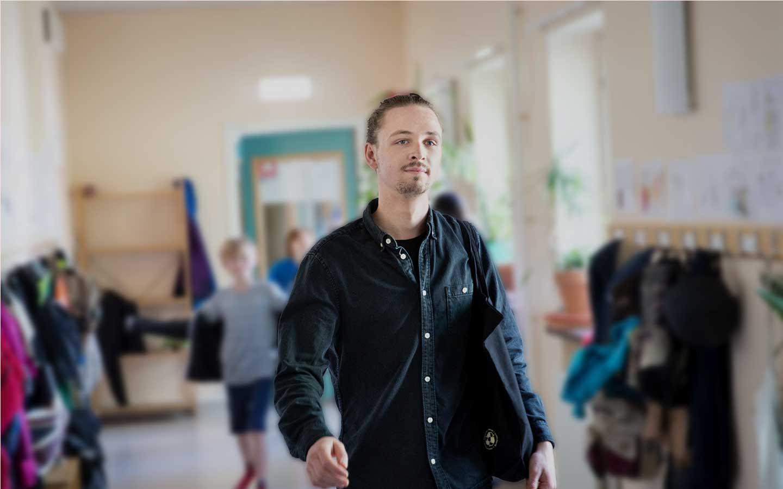 en man som är vikarie och går i en skolkorridor med glada barn i bakgrunden