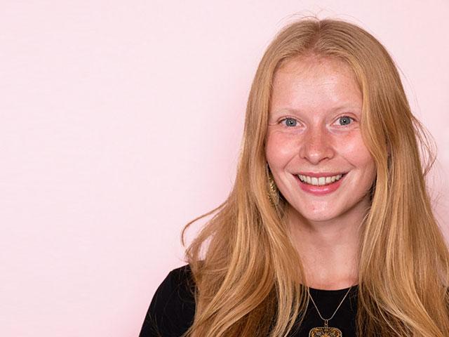 en glad ung kvinna som är fotograferad mot rosa bakgrund tittar in i kameran och ler