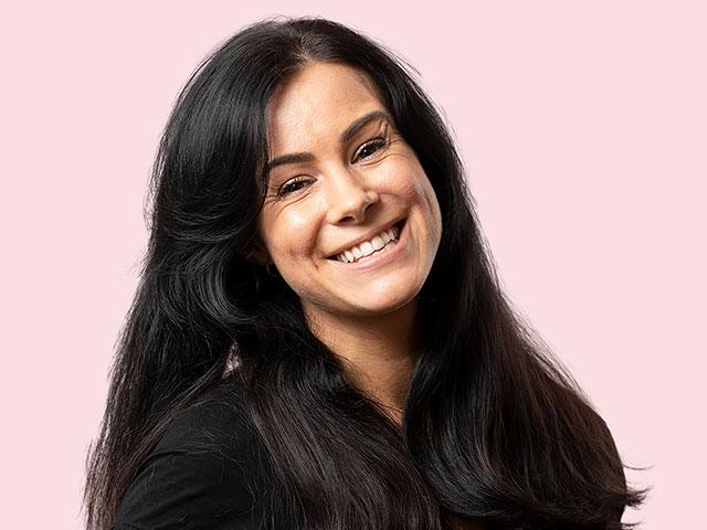 en glad, ung kvinna som är vikarie och är fotograferad mot rosa bakgrund