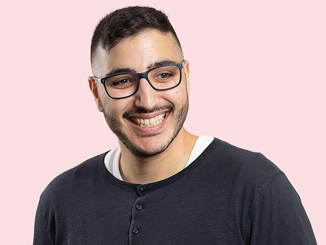en ung man som är en glad vikarie och fotograferad mot rosa bakgrund